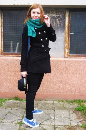 black coat - black hat - green scarf - blue bag - black pants - blue sneakers